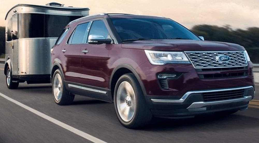Dark plum colored 2019 Ford Explorer tows a black trailer