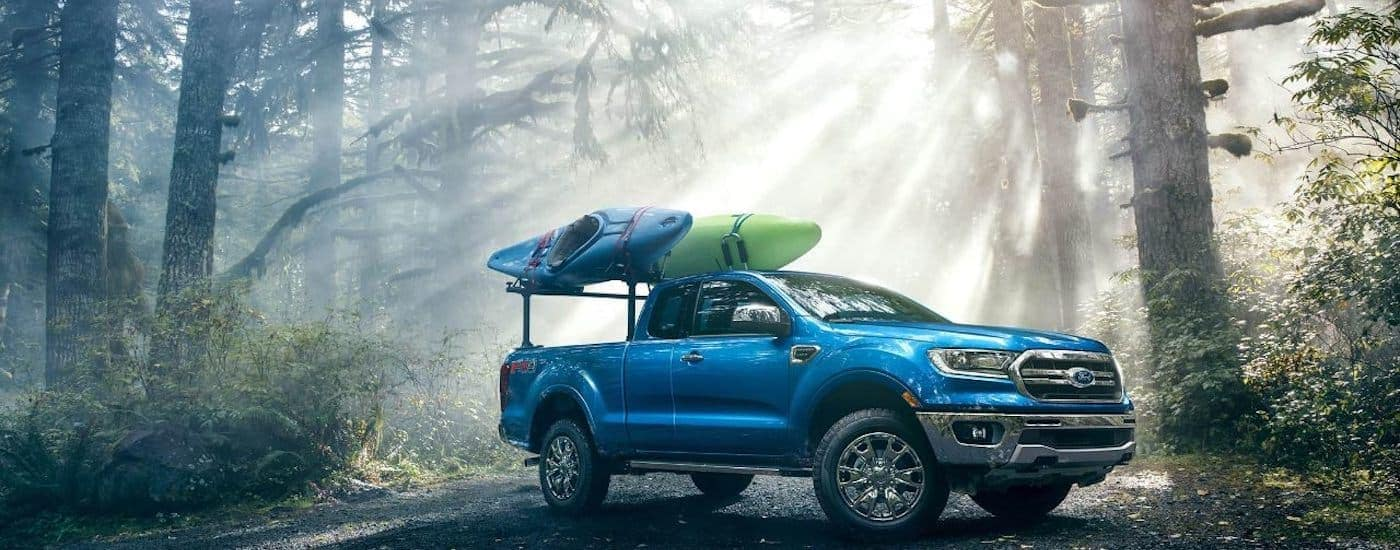 A bright blue 2019 Ford Ranger parked in the woods with kayaks on roof racks