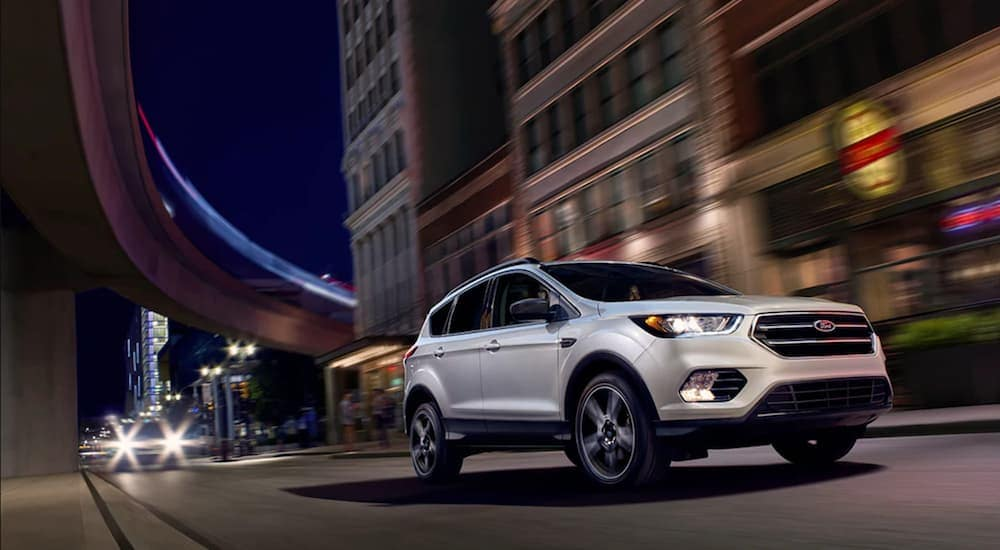 A white 2019 Ford Escape cruises a city street under a star filled sky