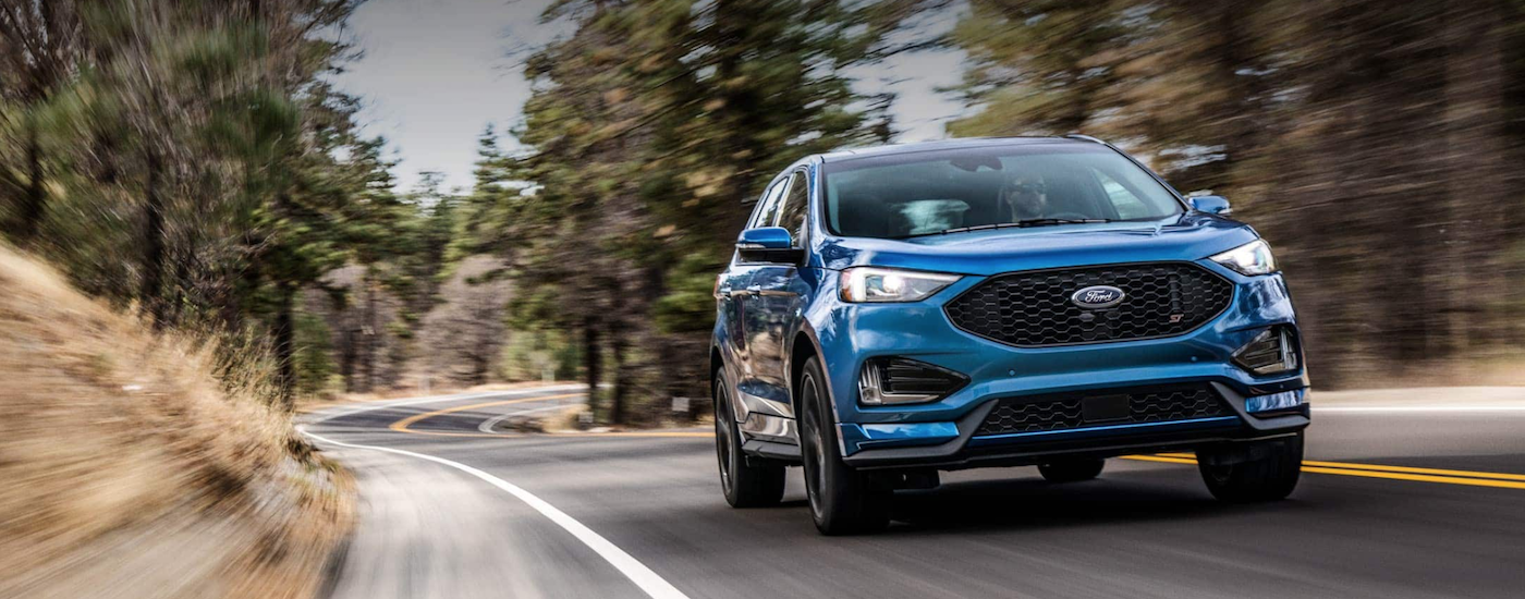 A blue 2019 Ford Edge is driving along a paved road in front of trees. You can check one out at a Ford dealership in Illinois near you.