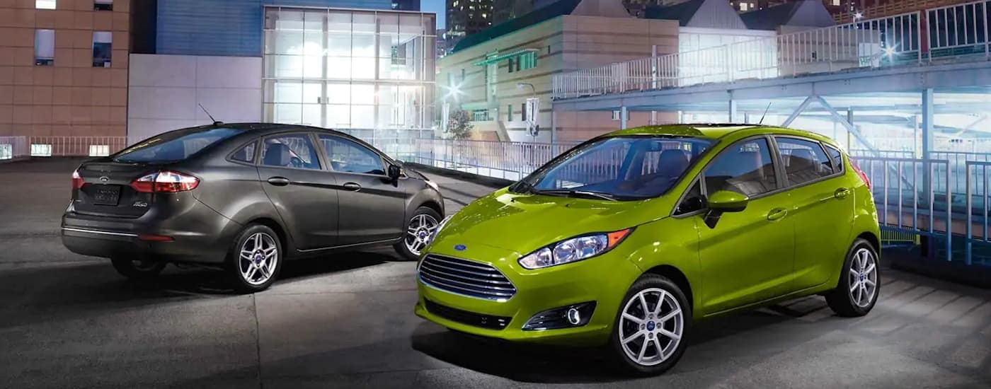 A grey 2019 Ford Fiesta is parked next to a green Fiesta hatchback on a top level parking deck. Check one out by searching 'Ford Dealerships Near Me - Carbondale, IL'.