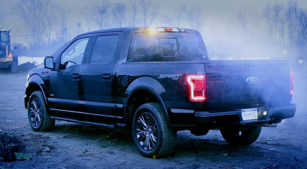 A Black 2016 Ford F-150 parked in a work area with a foggy background is shown.