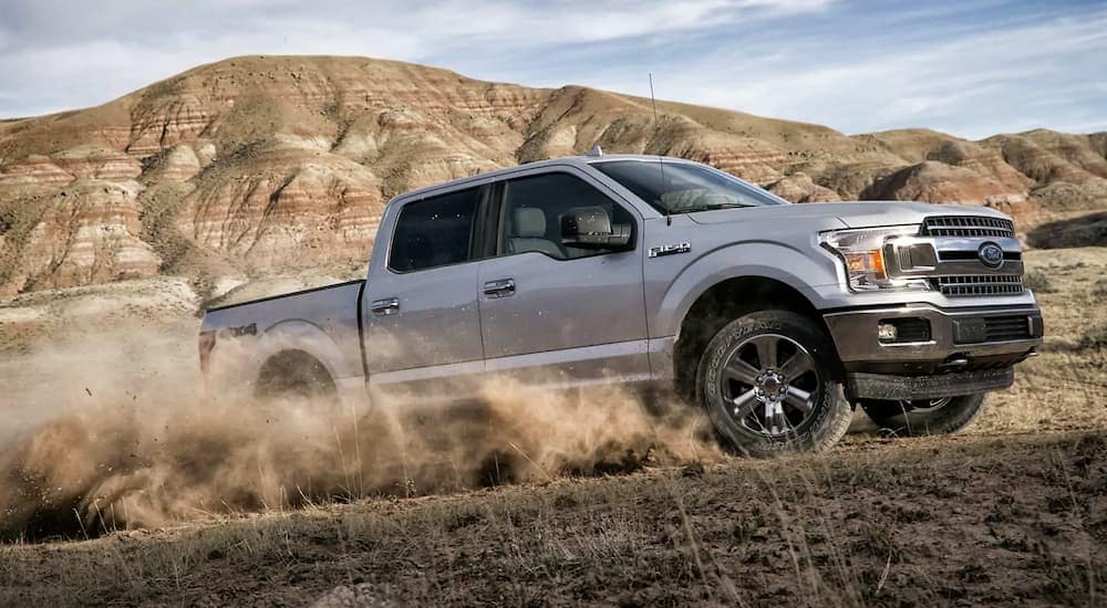 A silver 2019 Ford F-150, popular among options for a new Ford for sale, is driving in the desert.