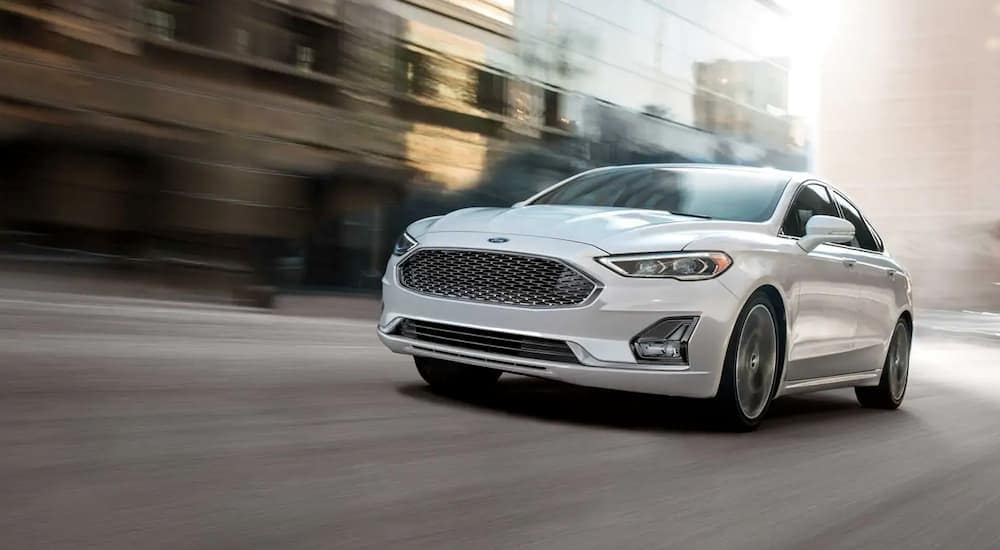 A white 2019 Ford Fusion is driving down a city block near Carbondale, IL.