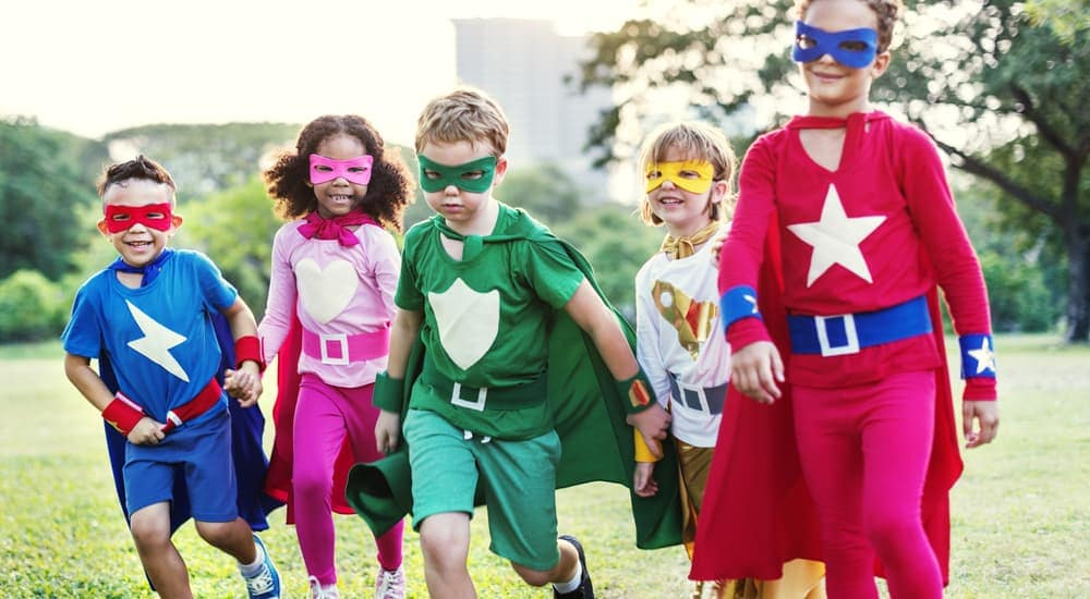 Five kids dressed as superheros are running in a field.