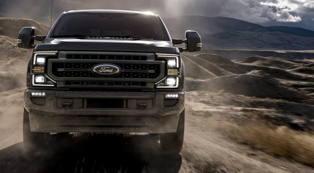 A black 2020 Ford Super Duty is driving on a dirt road near Carbondale, IL.