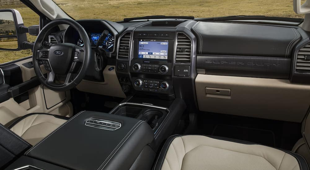 The front black and tan leather interior of the 2020 Ford Super Duty with a touchscreen.