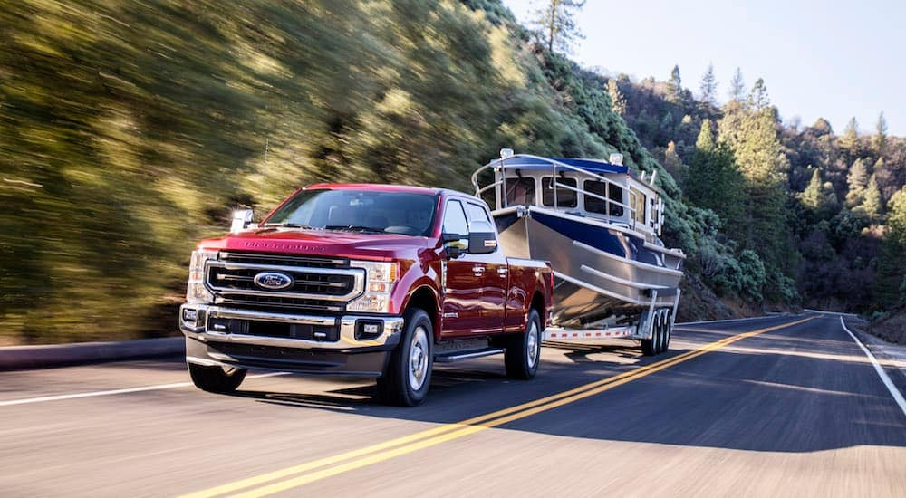 A red 2020 Ford Super Duty towing a large boat is shown.