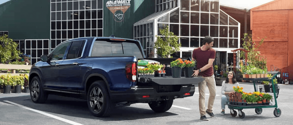 2020 Honda Ridgeline cargo space in truckbed man loading landscaping materials
