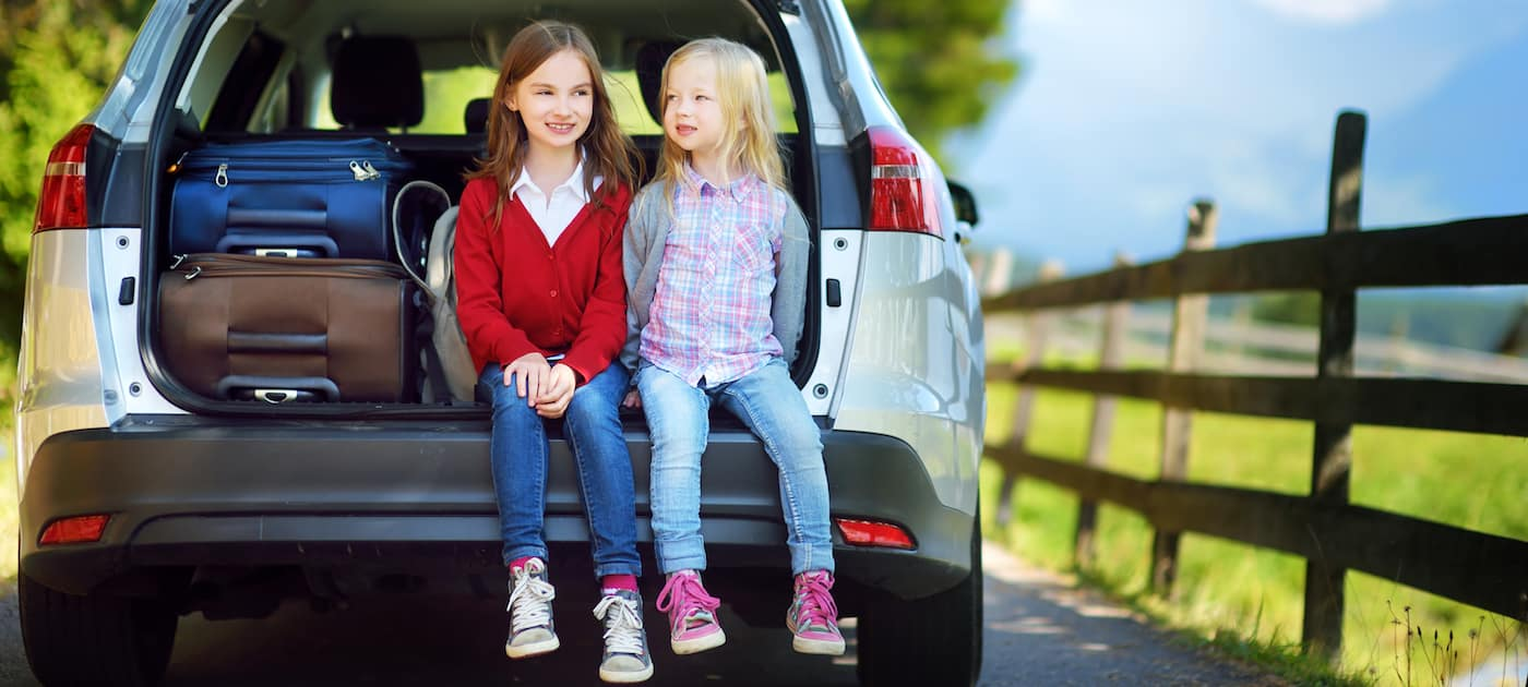 Two adorable little sitting in a car before going on vacations with their parents. Two kids looking forward for a road trip or travel.