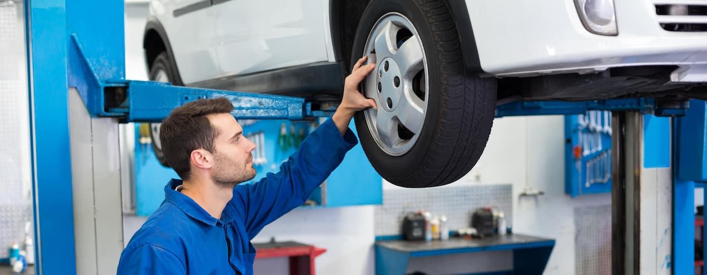 Mechanic looking at car tires at the repair garage